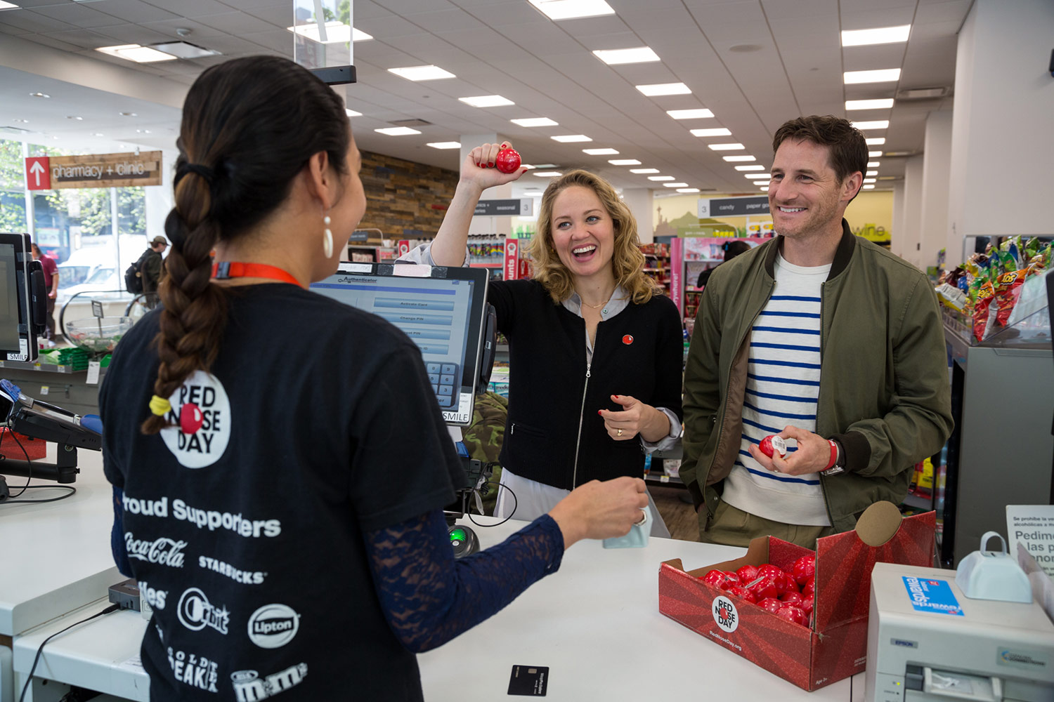 Two visitors celebrate purchasing Red Noses at a Walgreens store.