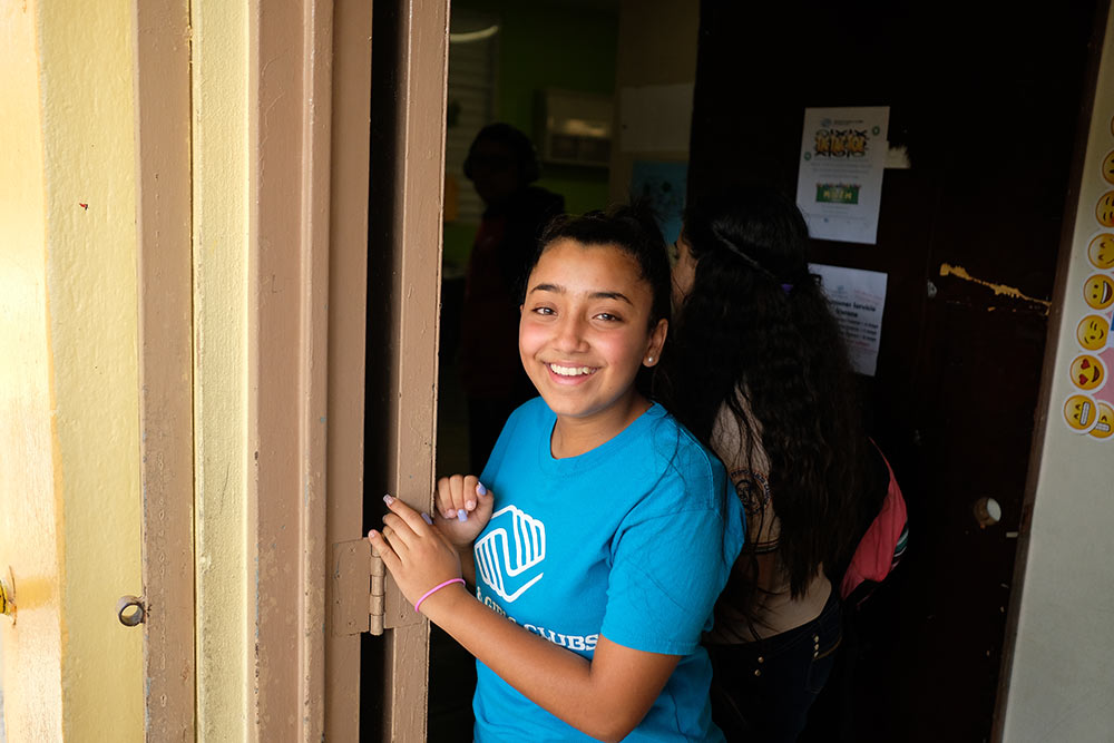Gabriela stands at the entrance to the Boys & Girls Club in Puerto Rico.