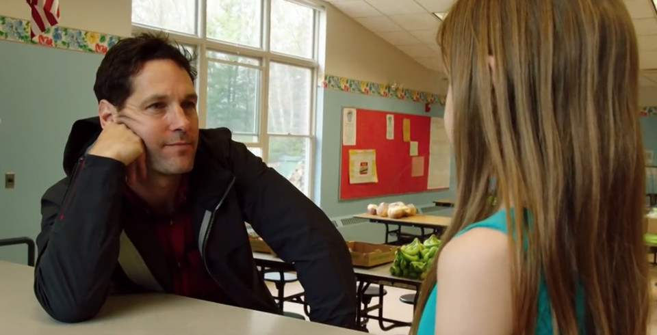 Paul Rudd speaks to a young girl at a school.